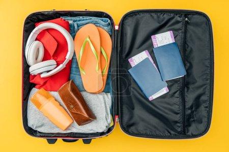 Foto de Vista superior de paja auriculares, pasaportes y entradas de aire en bolsa de viaje aislado sobre fondo amarillo - Imagen libre de derechos