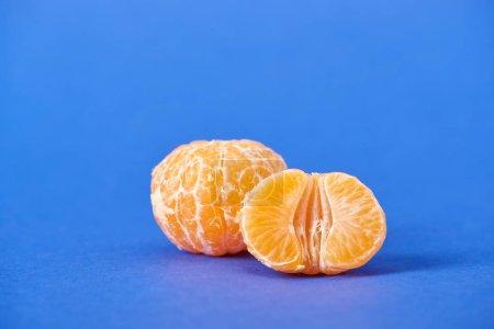 Photo pour La moitié de mandarine Pelée près de Clémentine entière sur fond bleu - image libre de droit