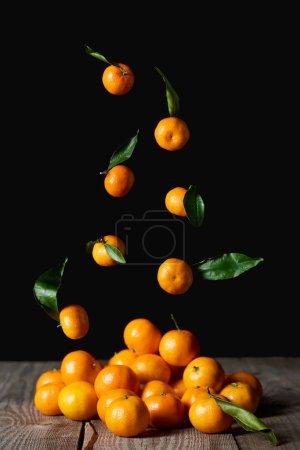 Photo pour Tangerines orange savoureuses avec des feuilles vertes, tombant sur une table en bois isolée sur fond noir - image libre de droit