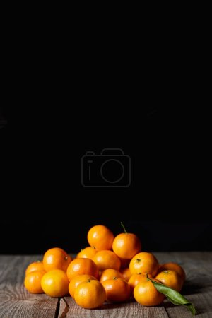 Photo for Tasty orange tangerines with green leaf on wooden table isolated on black - Royalty Free Image
