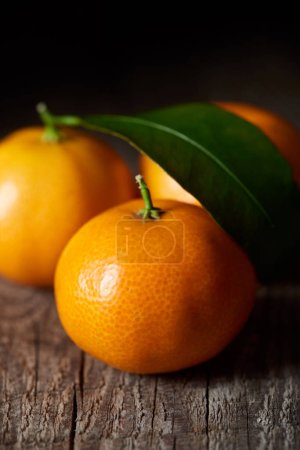 Photo pour Mise au point sélective de délicieuses mandarines sur table en bois - image libre de droit