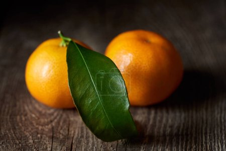 Photo for Selective focus of green leaf on organic tasty tangerine on wooden table - Royalty Free Image
