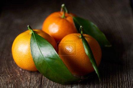 Photo pour Mise au point sélective d'organiques tangerines savoureux avec des feuilles vertes sur table en bois - image libre de droit