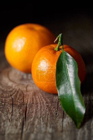 Photo for Selective focus of green leaf on tasty tangerine on wooden table - Royalty Free Image