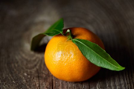 Photo for Selective focus of tasty tangerine with green leaves on wooden table - Royalty Free Image