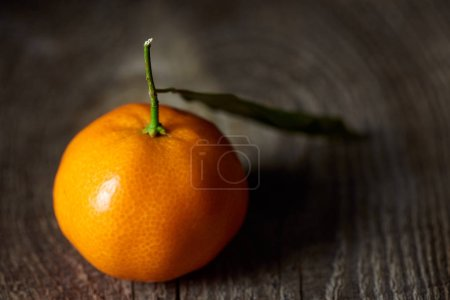 Photo pour Mise au point sélective de mandarine fraîche avec une feuille verte sur la table en bois - image libre de droit