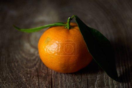 Photo pour Mise au point sélective de mandarine biologique avec des feuilles vertes sur table en bois - image libre de droit