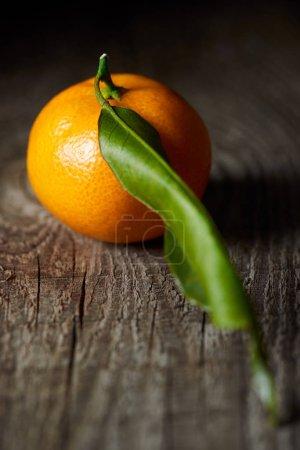 Photo pour Mise au point sélective de mandarine juteuse avec une feuille verte sur la table en bois - image libre de droit
