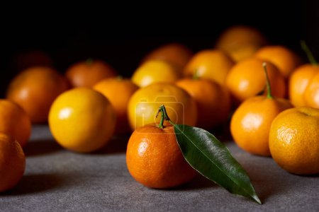 Photo for Selective focus of orange clementine with green leaf near tangerines on grey table - Royalty Free Image