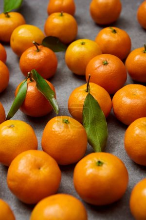 Photo for Selective focus of sweet tangerines with green leaves on grey table - Royalty Free Image