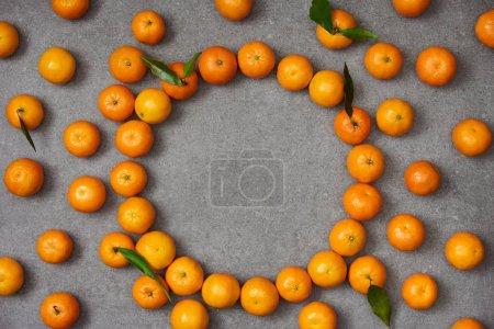Photo pour Vue de dessus de mandarines douces avec feuilles vertes sur table grise - image libre de droit