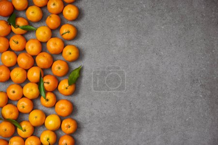 Photo for Top view of ripe organic clementines with green leaves on grey table - Royalty Free Image