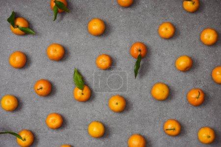 Photo pour Lay plat de mandarines sucrées avec des feuilles vertes sur table gris - image libre de droit