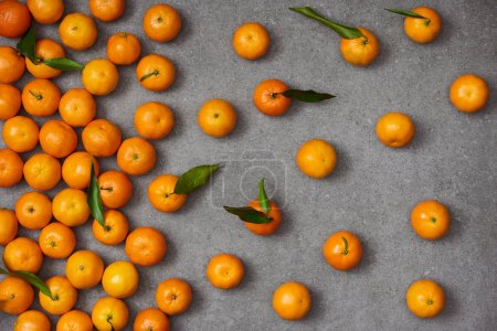 Photo for Top view of sweet orange tangerines with green leaves on grey table - Royalty Free Image