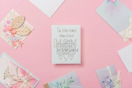 """Photo pour Carte de vœux blanche pour la fête des mères avec """"à la plus belle maman du monde"""" texte manuscrit et les cœurs, et diverses cartes postales disposées autour sur fond rose - image libre de droit"""