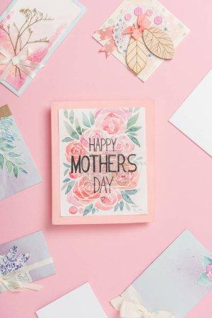 Photo pour Joyeuse carte de voeux de la fête des mères avec des fleurs, et diverses cartes postales de la fête des mères disposées autour sur fond rose - image libre de droit