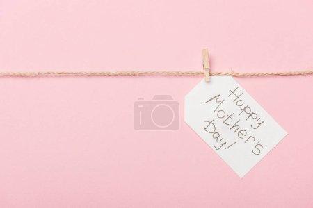 Photo pour Étiquette en papier blanc avec bonne fête des mères salutation avec fil grossier sur fond rose - image libre de droit