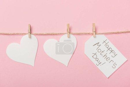 Photo pour Livre blanc coeurs et étiquette avec le message d'accueil de mères heureux jour avec filetage grossier sur fond rose - image libre de droit