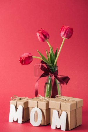 Photo for Bouquet of red tulips in glass vase and paper word mom on red background - Royalty Free Image