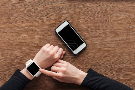 Partial view of woman using smartwatch with blank screen on wooden background