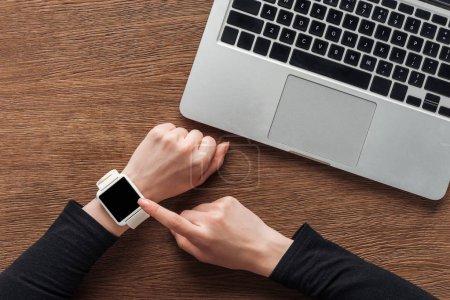 Photo pour Recadrée vue femme avec ordinateur portable et smartwatch avec écran blanc posant sur fond en bois - image libre de droit