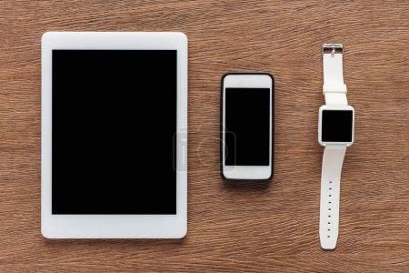 Photo pour Vue de dessus de tablette numérique, smartphone et smartwatch avec écran blanc sur fond en bois - image libre de droit