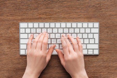 Partial view of woman typing on keyboard on wooden background