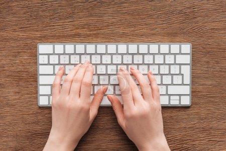 Photo pour Vue partielle de la femme tapant sur le clavier sur fond en bois - image libre de droit