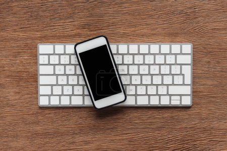 Photo for Top view of keyboard and smartphone with blank screen on wooden background - Royalty Free Image