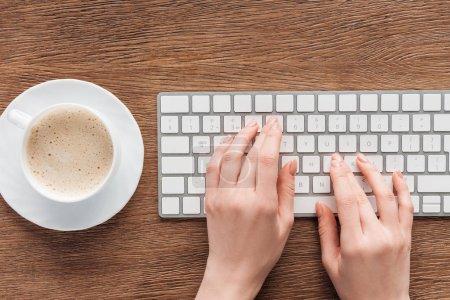 Photo pour Vue recadrée de fille tapant sur le clavier sur fond en bois - image libre de droit