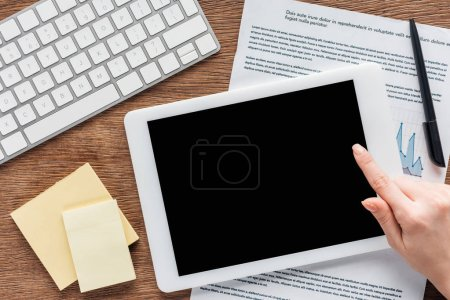Photo pour Vue partielle de la femme utilisant une tablette numérique avec écran blanc sur le lieu de travail - image libre de droit