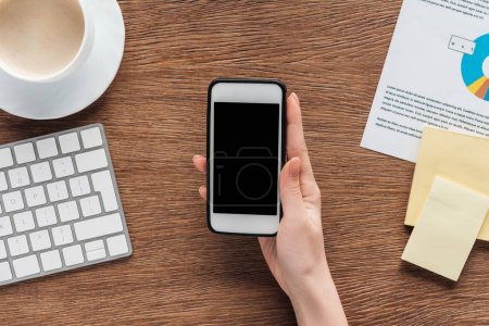 Photo for Cropped view of woman using smartphone with blank screen at workplace - Royalty Free Image