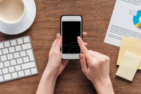 Photo for Cropped view of girl using smartphone with blank screen at workplace - Royalty Free Image