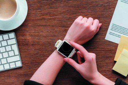 Photo pour Vue recadrée de la fille en utilisant smartwatch avec écran blanc sur fond en bois - image libre de droit