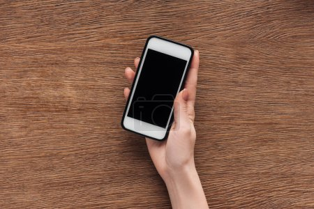 Photo for Partial view of woman holding smartphone with blank screen on wooden background - Royalty Free Image
