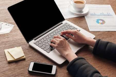 Photo pour Vue recadrée de la femme tapant sur le clavier de l'ordinateur portable au travail - image libre de droit