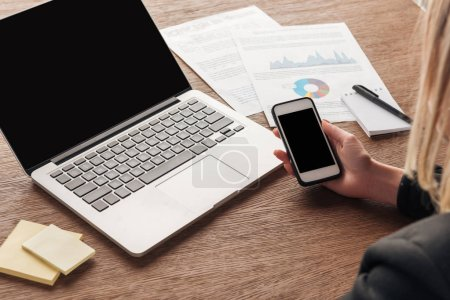 Photo for Partial view of woman using smartphone with blank screen at workplace - Royalty Free Image