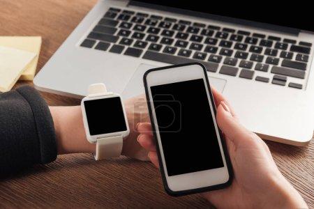 Photo pour Vue partielle de la femme avec le portable, smartwarch et smartphone avec écran blanc - image libre de droit