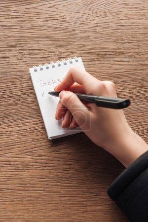 Photo pour Recadrée vue de femme écrivant en ordinateur portable sur une surface en bois - image libre de droit