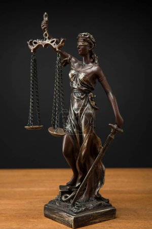 Photo for Bronze statuette with scales of justice on wooden table isolated on black - Royalty Free Image