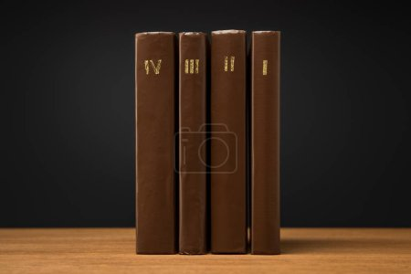 Photo for Volumes of old books in leather brown covers on wooden table isolated on black - Royalty Free Image