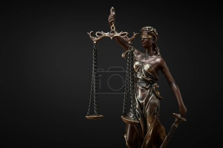 Photo for Bronze statuette with scales of justice isolated on black - Royalty Free Image