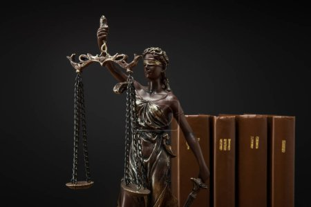 Photo for Bronze statuette with scales of justice and volumes of brown books isolated on black - Royalty Free Image