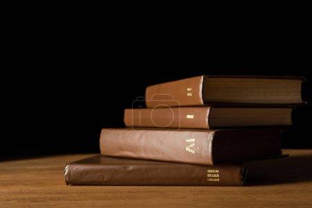 Photo pour Foyer sélectif de livres en cuir marron sur table en bois isolé sur noir - image libre de droit