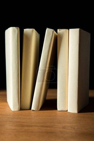 Photo pour Rangée de livres en papier blanc couvre sur table en bois isolé sur noir - image libre de droit