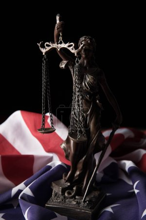 Photo for Bronze statuette with scales of justice and american flag isolated on black - Royalty Free Image