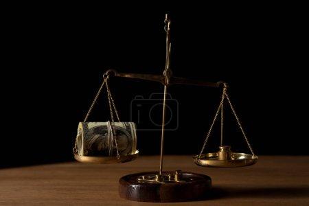 Photo pour Trésorerie rouleau de billets de dollar et poids sur des échelles de vintage doré sur une table en bois isolé sur fond noir - image libre de droit