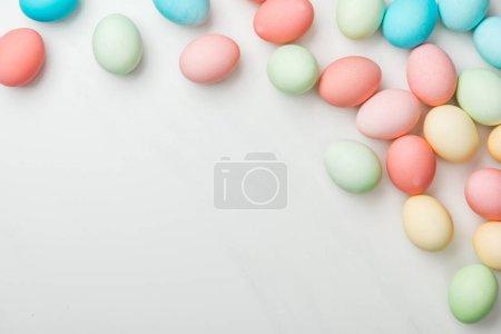 Photo pour Vue de dessus des oeufs de Pâques pastel épars sur blanc avec espace de copie - image libre de droit