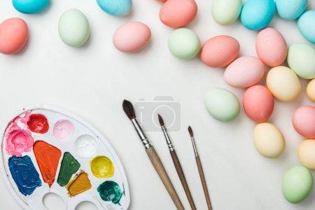 Photo pour Vue de dessus des oeufs de Pâques pastel avec la palette de couleurs et pinceaux isolé sur blanc - image libre de droit