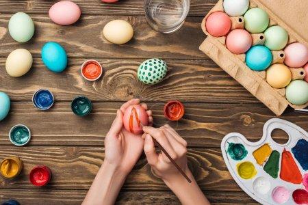 Photo pour Vue de dessus de femme décoration oeufs de Pâques avec un pinceau à table en bois avec la palette de couleurs et de peintures - image libre de droit